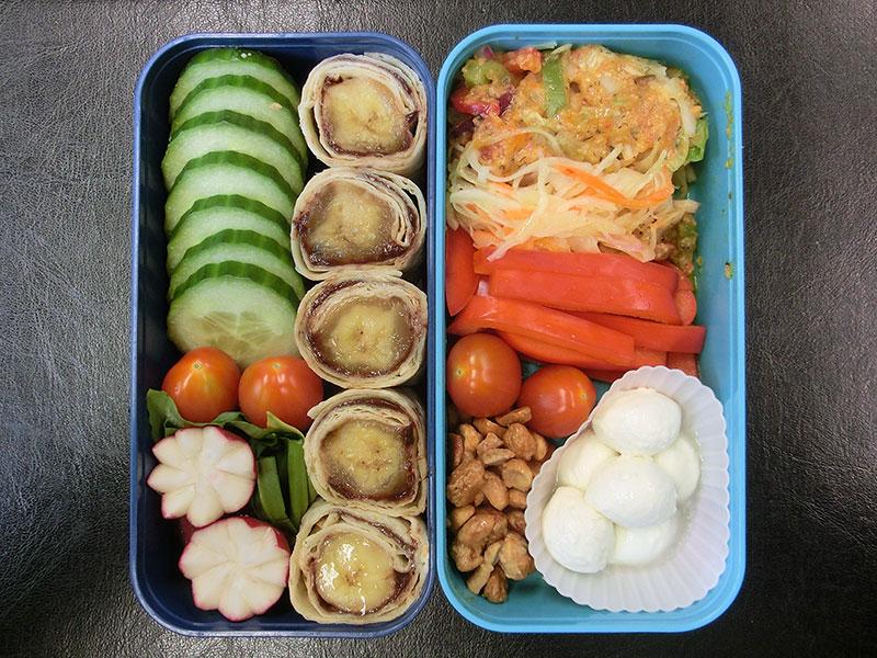 Bento Box gefüllt mit Gurke, Tomaten, Radieschen, Bananen Wrap, Salat, Paprika, Erdnüsse, Mozzarella