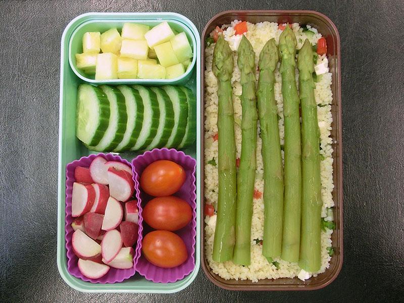 Bento Box gefüllt mit Spargel, Bulgur, Ananas, Gurke, Radieschen, Tomaten