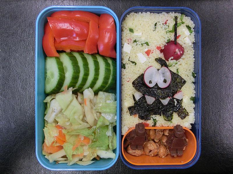 Bento Box gefüllt mit Cour cous, Radieschen, Erdnüsse, Schokolade, Paprika, Gurke, Salat