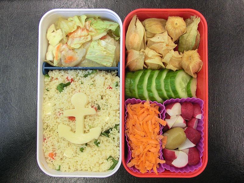 Bento Box gefüllt mit Cous cous, Salat, Physalis, Gurke, Möhren, Radieschen