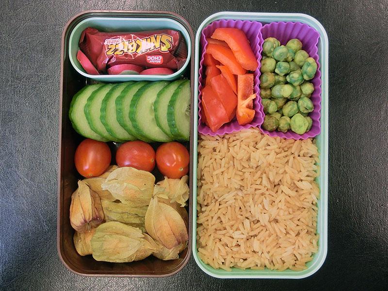 Bento Box gefüllt mit Reis, Wasabi-Erbsen, Gurke, Tomaten, Physalis, Schokolade