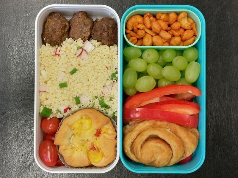 Bento Box gefüllt mit Hackbällchen, Cous cous, Pie, Tomaten, Nüsse, Weintrauben, Paprika, Franzbrötchen