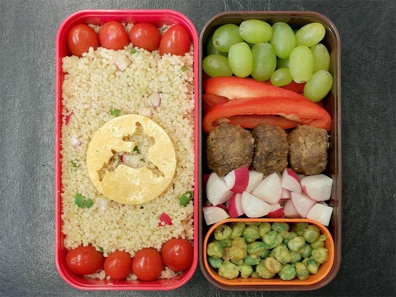 Bento Box gefüllt mit Cous cous, Tomaten, Weintrauben, Käse, Paprika, Hackbällchen, Radieschen, Wasabi-Erbsen