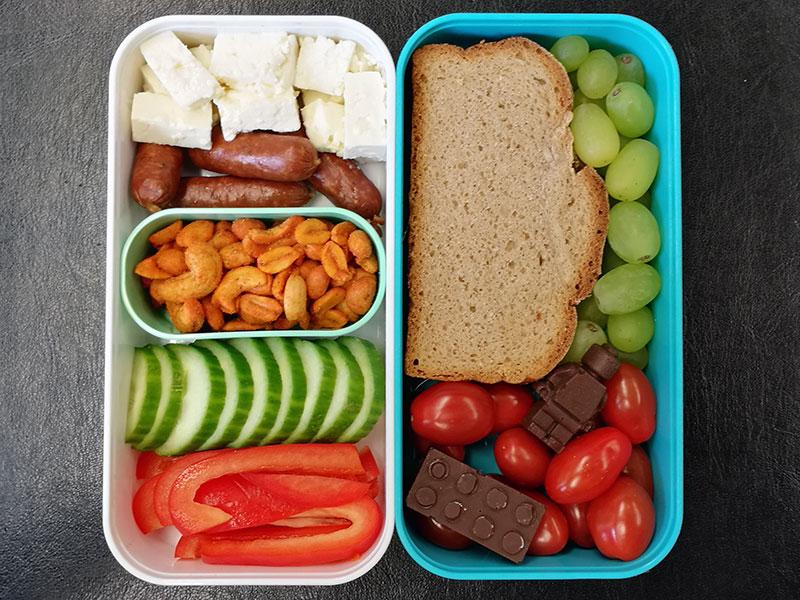Bento Box gefüllt mit Butterbrot, Weintrauben, Tomaten, Schokolade, Schafskäse, Cabanossi, Erdnüsse, Gurke, Paprika