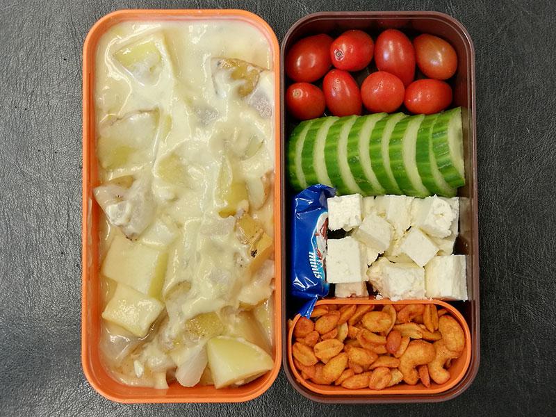 Bento Box gefüllt mit Kartoffelpfanne, Tomaten, Gurke, Schafskäse, Schokolade, Erdnüsse