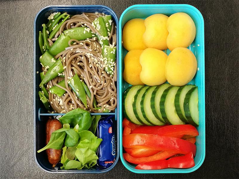 Bento Box gefüllt mit Aprikosen, Gurke, Paprika, Nudelpfanne, Kabanossi, Schokolade