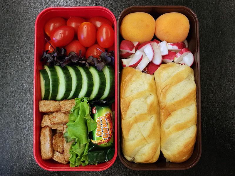 Bento Box gefüllt mit Brötchen, Radieschen, Aprikosen, Tomaten, Gurke, Hähnchen, Schokolade