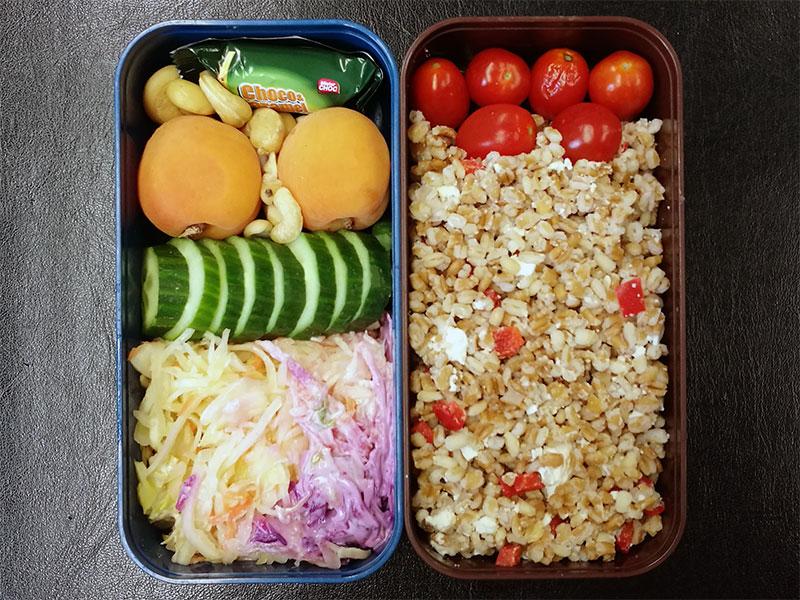 Bento Box gefüllt mit Bulgur, Tomaten, Aprikosen, Nüsse, Schokolade, Krautsalat, Gurke