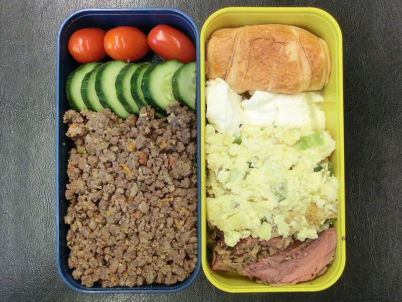 Bento Box gefüllt mit Gurke, Beef Tea, Kartoffelsalat, Brötchen, Büffelmozzarella, Roastbeef