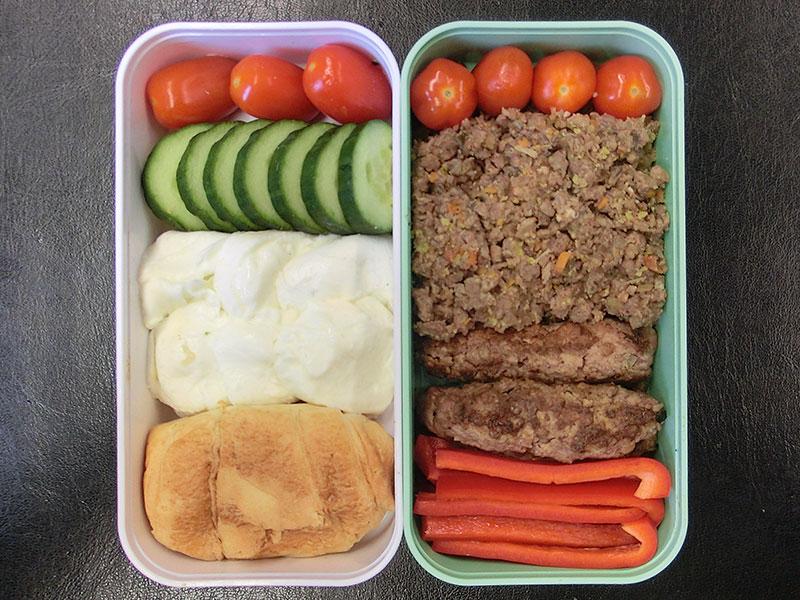 Bento Box gefüllt mit Büffelmozzarella, Tomaten, Gurke, Beef Tea, Hackröllchen, Paprika, Brötchen