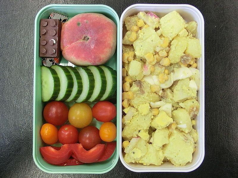 Bento Box gefüllt mit Kartoffelsalat, Tomate, Paprika, Gurke, Pfirsich, Schokolade