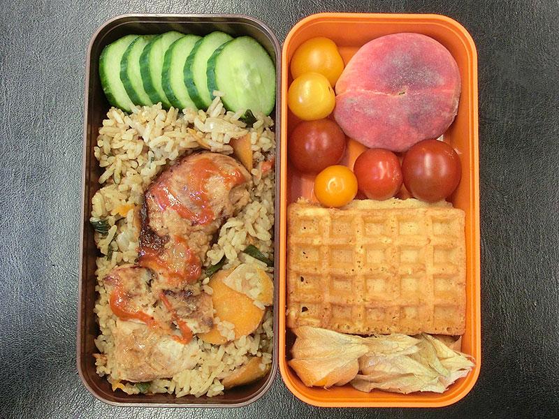 Bento Box gefüllt mit Gurke, Reispfanne, Hühnchen, Pfirsich, Tomaten, Waffel, Physalis