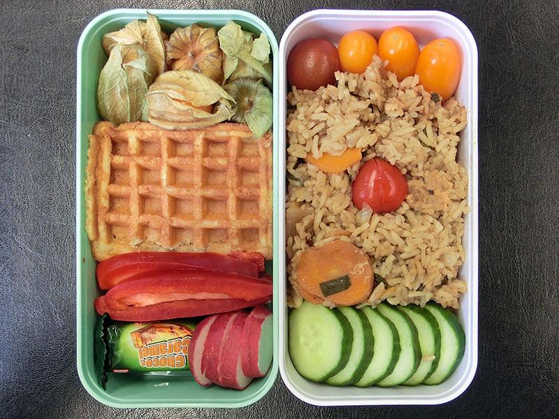 Bento Box gefüllt mit Physalis, Waffel, Paprika, Radieschen, Schokolade, Tomaten, Reispfanne, Gurke