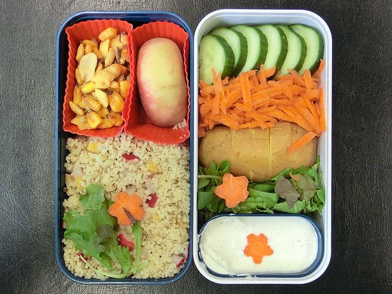 Bento Box gefüllt mit Couscous, Nüsse, Pfirsisch, Gurke, Möhren, Kartoffel, Sour Cream
