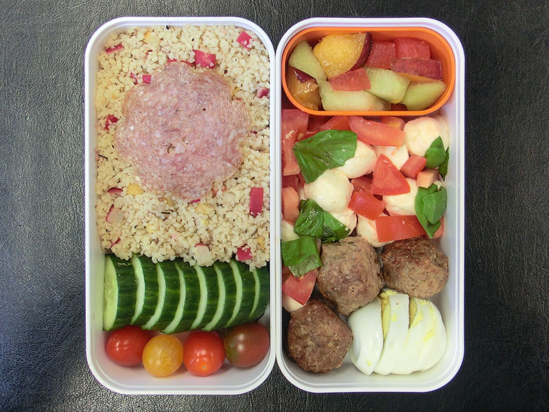 Bento Box gefüllt mit Couscous, Gurke, Tomaten, Obstsalat, Mozzarella, Hackbällchen, Ei