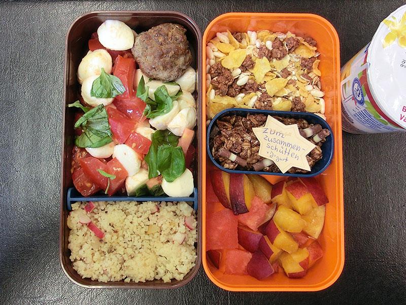 Bento Box gefüllt mit Müsli, Joghurt, Tomate, Mozzarella, Cous Cous