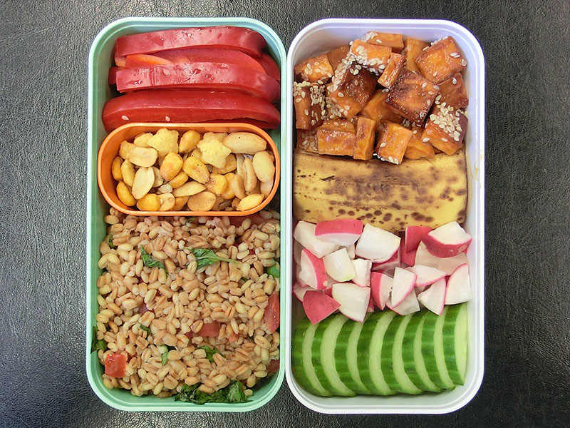 Bento Box gefüllt mit Paprika, Nüsse, Bulgur, Süßkartoffeln, Banane, Radieschen, Gurke