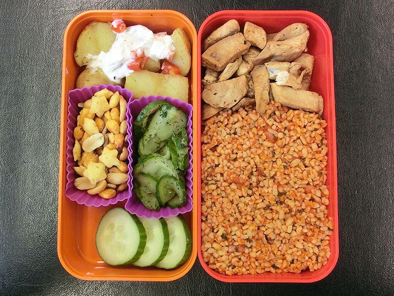 Bento Box gefüllt mit Putenstreifen, Cous cous, Kartoffeln, Gurke, Nüsse, Gurke