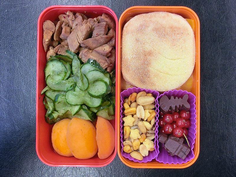 Bento Box gefüllt mit Putenstreifen, Gurke, Pfirsich, Brötchen, Nüsse, Johannisbeeren, Schokolade