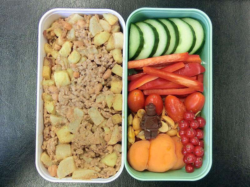 Bento Box gefüllt mit Kartoffelpfanne, Gurke, Paprika, Tomaten, Nüsse, Johannisbeeren, Pfirsich, Schokolade