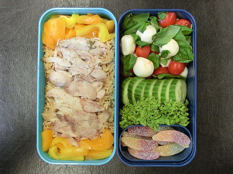 Bento Box gefüllt mit Reispfanne,Hähnchen,Paprika,Tomaten,Mozzarella,Gurke,Weingummi