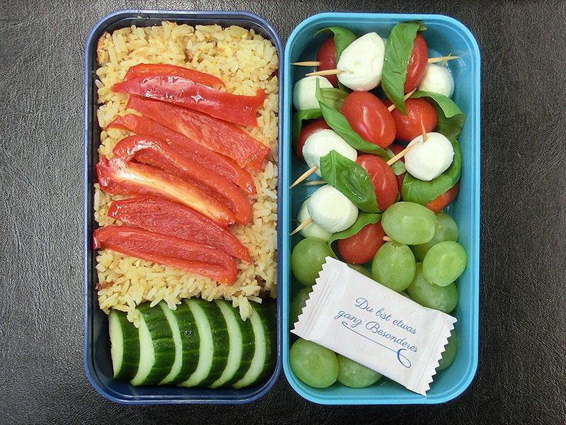 Bento Box gefüllt mit Reispfanne, Paprika, Gurke, Weintrauben, Tomaten, Mozzarella, Schokolade