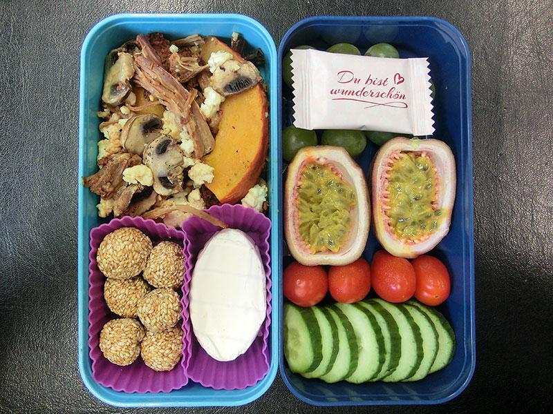 Bento Box gefüllt mit Pilzpfanne, Sesambällchen, Käse, Gurke, Tomaten, Maracuja, Weintrauben, Schokolade