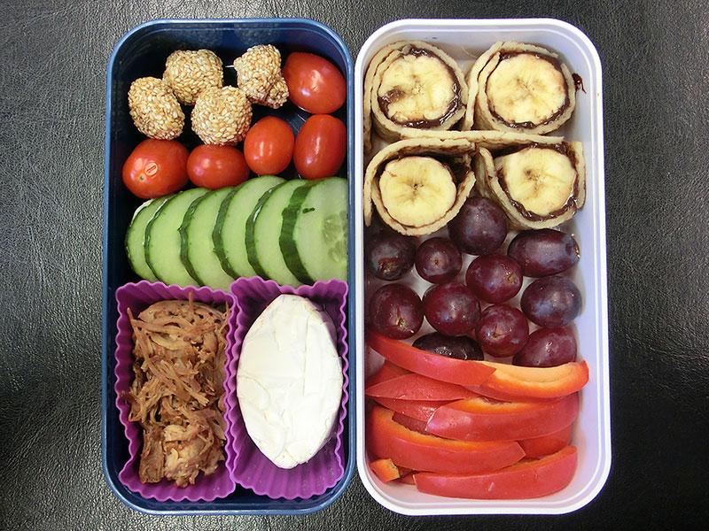 Bento Box gefüllt mit Sesambällchen, Tomaten, Gurke, Pulled Pork, Bananenwraps, Weintrauben, Paprika
