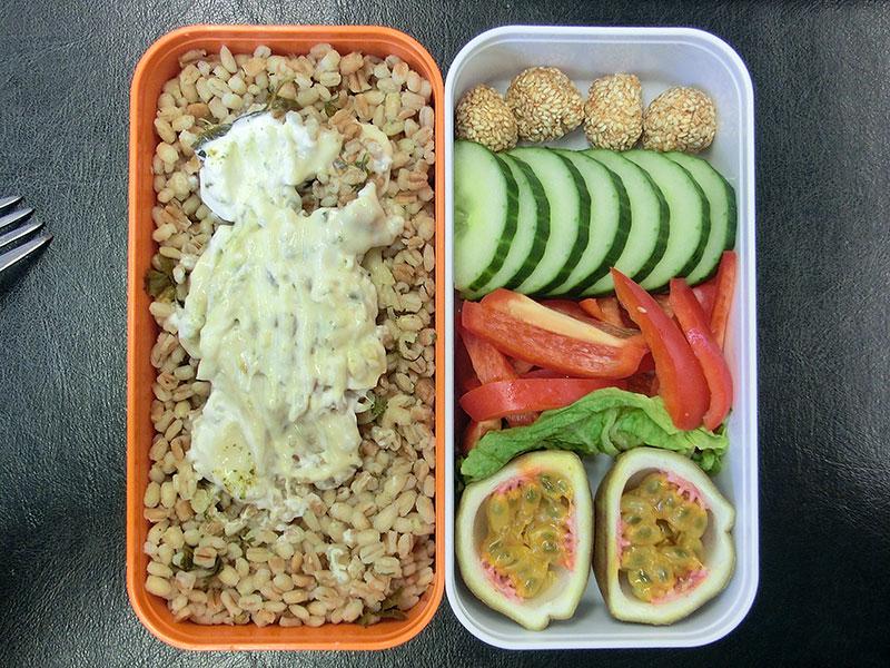 Bento Box gefüllt mit Bulgur, Sesambällchen, Gurke, Paprika, Maracuja