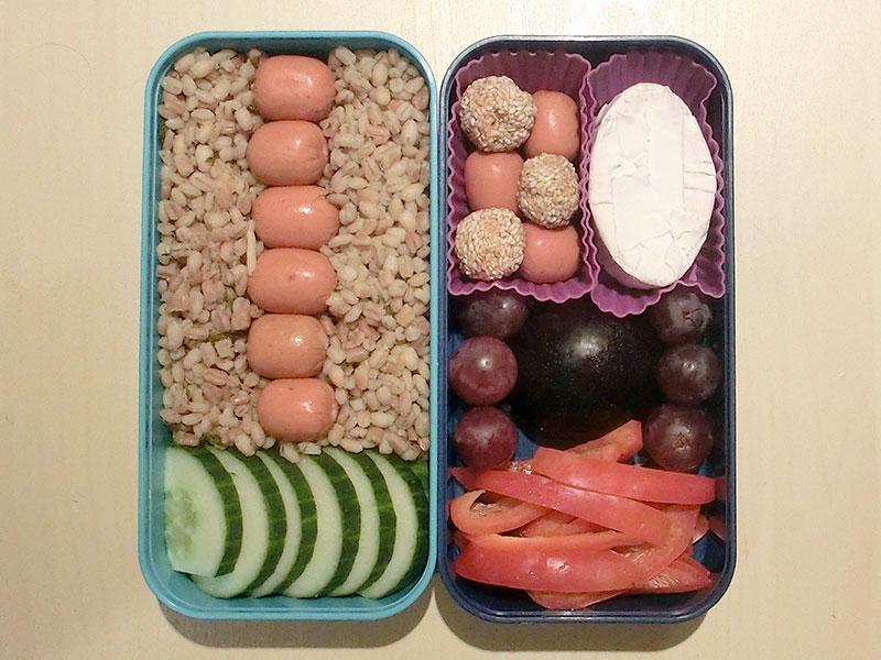 Bento Box gefüllt mit Bulgur, Würstchen, Gurke, Sesambällchen, Käse, Weintraube, Pflaume, Paprika