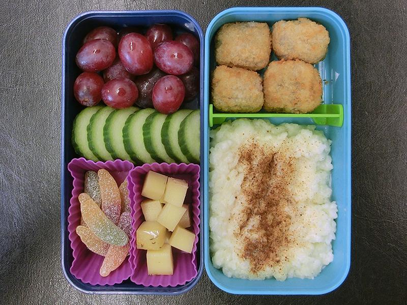Bento Box gefüllt mit Weintrauben, Gurke, Käse, Kartoffelsnacks, Milchreis, Weingummi