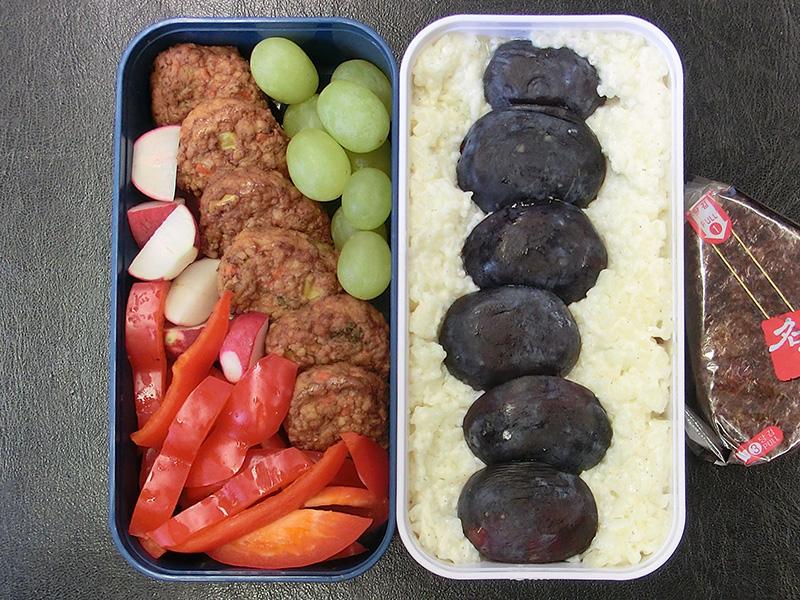 Bento Box gefüllt mit Frikadellen, Paprika, Radieschen, Milchreis, Pflaumen, Weintrauben, Onigiri