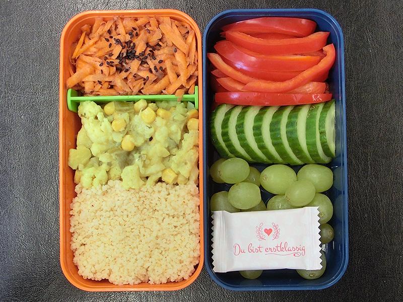 Bento Box gefüllt mit Cous cous, Kartoffelsalat, Karotten, Paprika, Gurke, Weintrauben, Schokolade