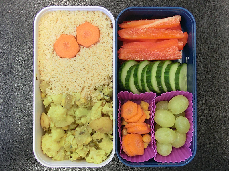 Bento Box gefüllt mit Möhre, Cous cous, Kartoffelsalat, Paprika, Gurke, Weintrauben