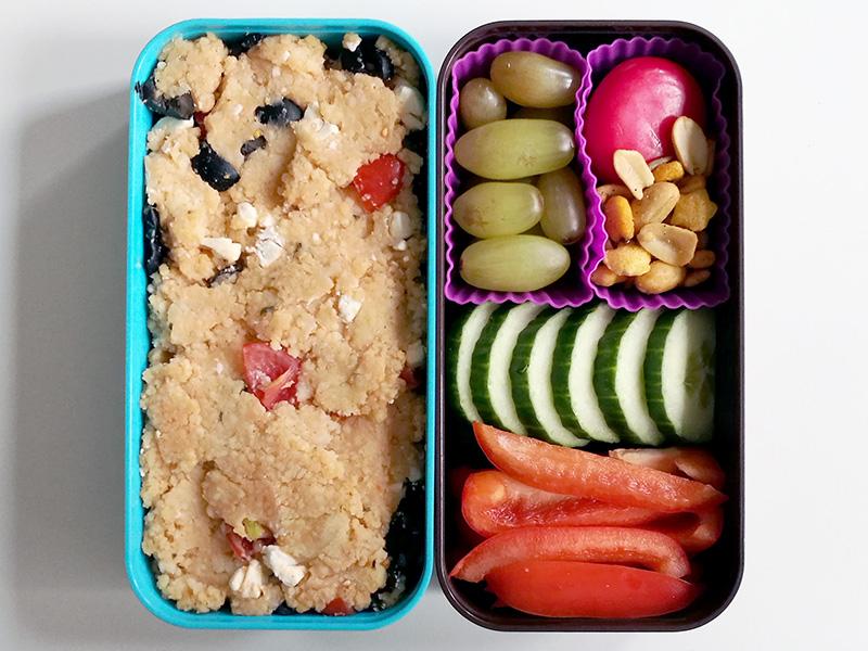 Bento Box gefüllt mit Cous Cous, Weintrauben, Babybel, Nüsse, Gurke, Paprika