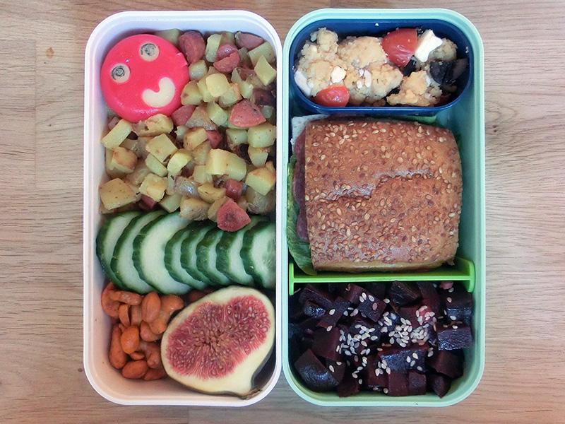 Bento Box gefüllt mit Cous Cous, Sandwisch, Rote Beete, Babybel, Kartoffelpfanne, Gurke, Nüsse, Feige
