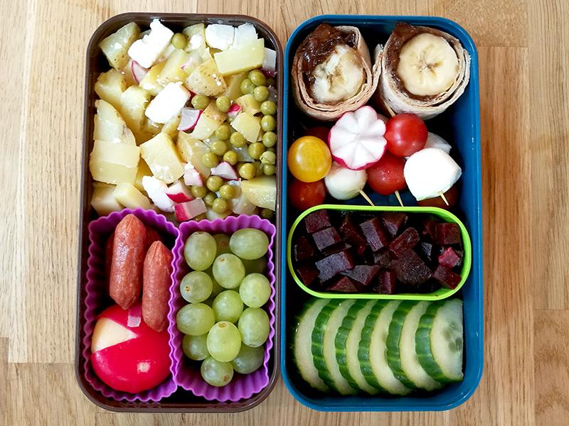 Bento Box gefüllt mit Kartoffelpfanne, Weintrauben, Cabanossi, Babybel, Bananencrepes, Rote Beete, Tomaten, Mozarella, Gurke