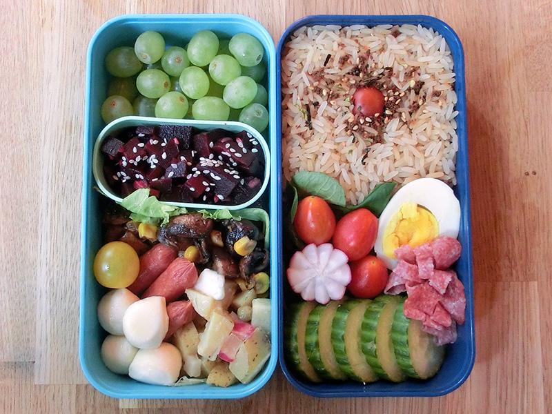 Bento Box gefüllt mit Reis, Ei, Tomaten, Gurke, Weintrauben, Rote Beete, Obstsalat, Tomaten, Mozarella