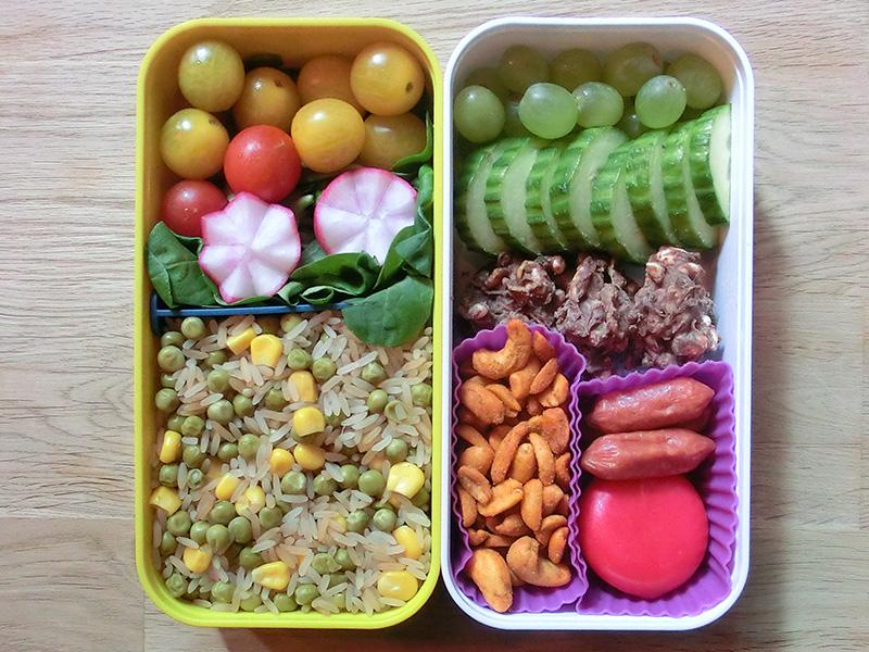 Bento Box gefüllt mit Tomaten, Radieschen, Reispfanne, Weintrauben, Gurke, Schokolade, Nüsse, Babybel, Cabanossi