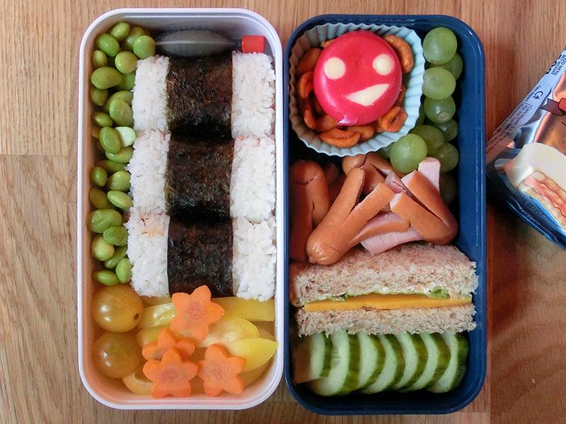 Bento Box gefüllt mit Sojabohnen, Onigiri, Paprika, Möhren, Tomaten, Weintrauben, Babybel, Nüsse, Würstchen, Sandwich, Gurke