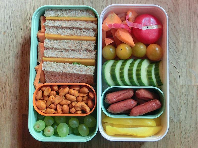 Bento Box gefüllt mit Sandwich, Möhren, Nüsse, Weintrauben, Babybel, Tomaten, Gurke, Cabanossi, Paprika