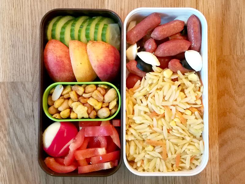 Bento Box gefüllt mit Cabanossi, Tomten, Nudeln, Gurke, Apfel, Nüsse, Paprika, Babybel