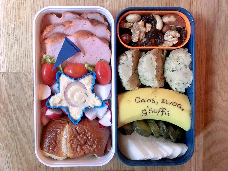 Bento Box gefüllt mit Leberkäse, Tomaten, Obazda, Laugenbrötchen, Nüsse, Knödel, Banane, Gewürzgurke, Rettich