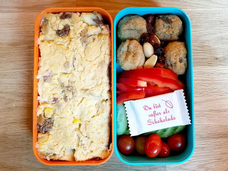 Bento Box gefüllt mit Shepards Pie, Falafel, Nüsse, Paprika, Gurke, Tomaten, Schokolade