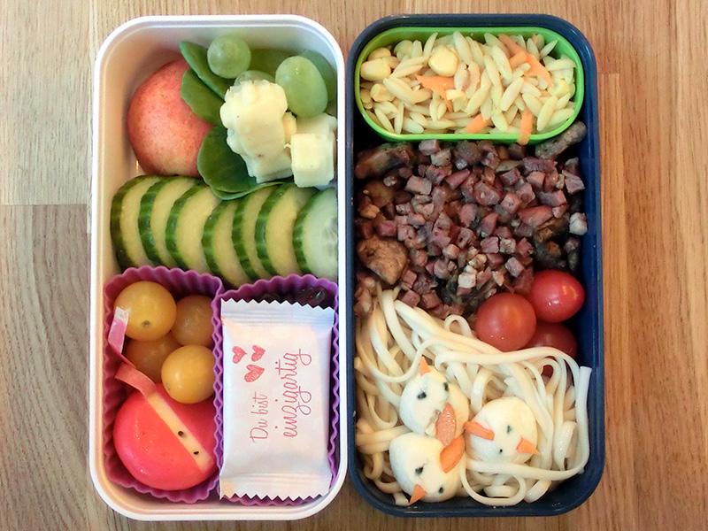 Bento Box gefüllt mit Käse, Weintrauben, Apfel, Gurke, Tomaten, Babybel, Nüsse, Schokolade, Nudeln, Pilzpfanne, Mozarella