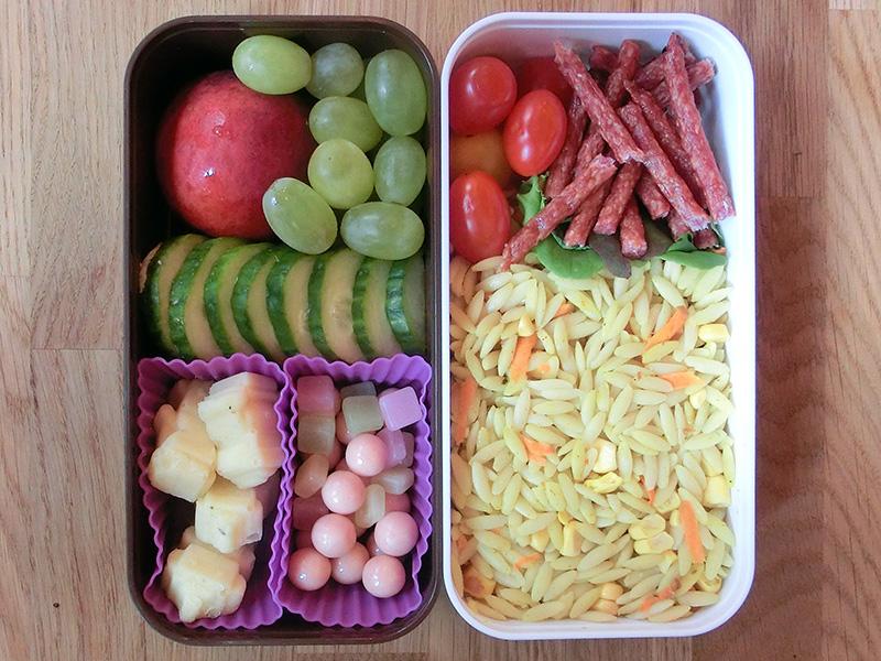 Bento Box gefüllt mit Aprikose, Weintrauben, Gurke, Käse, Salami, Nudeln