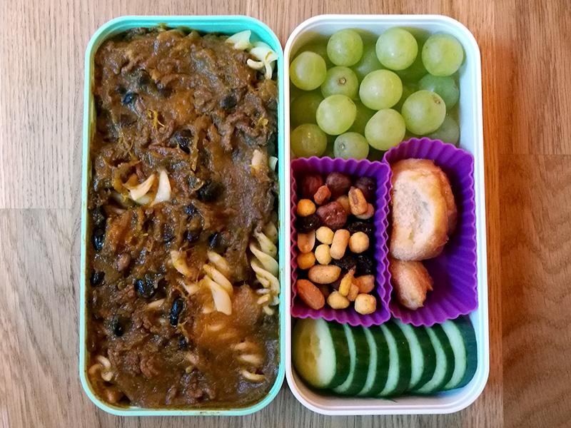 Bento Box gefüllt mit Chilli con Carne mit Nudeln, Weintrauben, Nüsse, Laugengebäck, Gurke