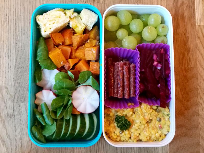 Bento Box gefüllt mit Süßkartoffeln, Radieschen, Gurke, Weintrauben, Salami, Rote Beete, Cous Cous
