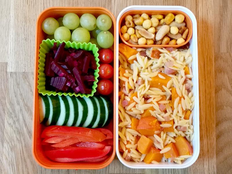 Bento Box gefüllt mit Weintrauben, Rote Beete, Tomaten, Gurke, Paprika, Nüsse, Kritharaki mit Süßkartoffeln