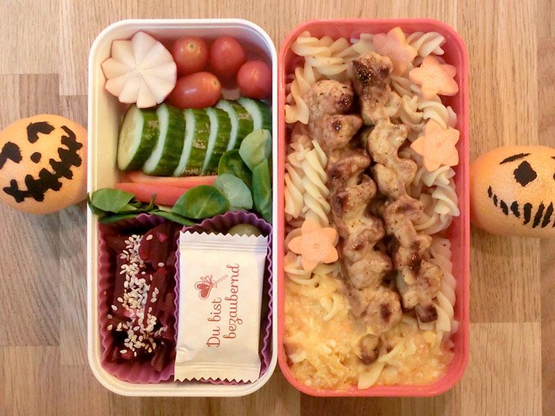 Bento Box gefüllt mit Tomaten, Radieschen, Gurke, Paprika, Weintrauben, Rote Beete, Schokolade, Nudeln, Geflügel
